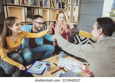 We did it. Jolly four colleagues exchanging high five and smiling