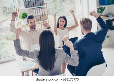 We did it! Success and winning concept - happy business team with raised up hands in light modern workstation, celebrating the breakthrough in their company