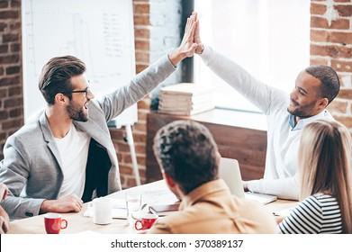 We did it! Two young men doing high-five while their coworkers sitting at the office table
