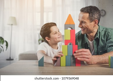 We did it together. Portrait of joyful father and son looking at each other with satisfaction while sitting near self-made toy tower