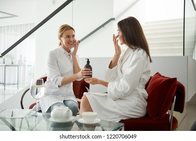 We are examining cosmetic product. Portrait of smiling beautician holding bottle with dispenser while sitting in chair and looking at brunette girl in white bathrobe
