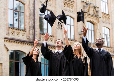 We are finally graduated! Four happy college graduates in graduation gowns throwing their mortar boards and smiling while standing near university