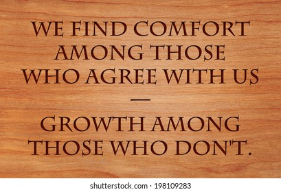 We find comfort among those who agree with us and growth among those who don't - quote on wooden red oak background