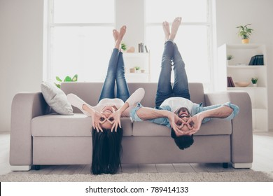 We go crazy and have fun together! Beautiful cheerful delightful humorous couple of two lovers clothed in casual denim outwear, demonstrating binoculars using hands, lying upside-down