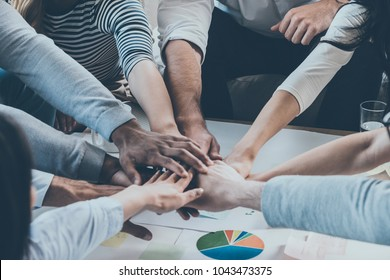 We are the great team! Group of happy business people holding hands together while sitting around the desk