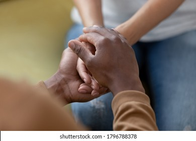 We handle this together. Close up top view of young biracial female palms in hands of black male lover, friend or partner. African married couple in love reconcile after quarrel, harmony in relations