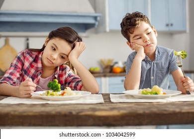 We hate vegetables. Attractive sad dark-haired little brother and sister sitting at the table and having healthy breakfast and looking sadly at the vegetables