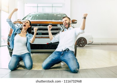 We are have a car! Happy young emotional couple in casual wear buying first new family car together in dealership.
