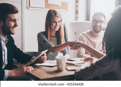 We have a deal! Two beautiful women shaking hands and looking at each other with smile while sitting at the business meeting with their coworkers