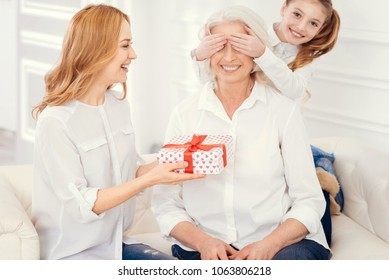 We have a gift for you. Full of love little girl covering up eyes of her cheerful grandmother while a radiant mother giving a beautifully wrapped present and congratulating the granny.
