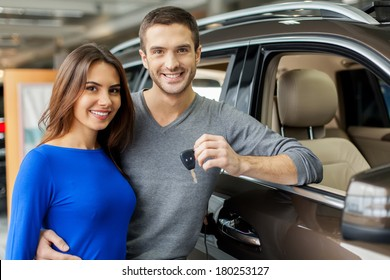 We have made the right choice. Handsome young men standing near the car at the dealership hugging his girlfriend and holding a key
