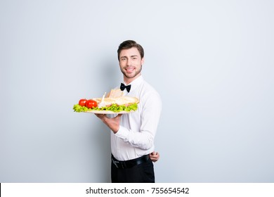 We have royal service in our restaurant, we are always ready to make you feel on cloud nine. Waiter is holding a large tray with an appetizer, isolated on grey background
