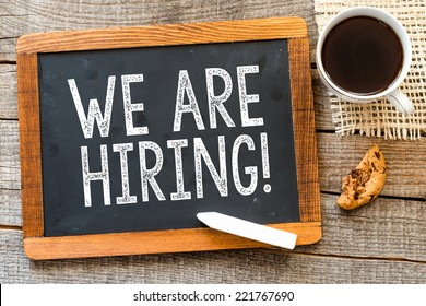 We are Hiring ! handwritten with white chalk on a blackboard, cup of coffee and biscuit on a wooden background