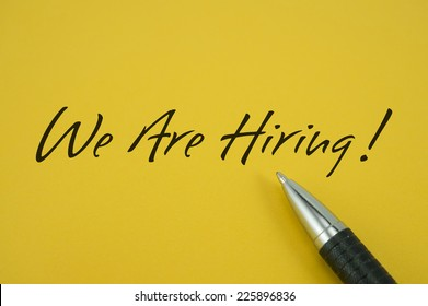 We Are Hiring! note with pen on yellow background