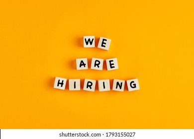 We are hiring text on wooden blocks against yellow background. Concept of human resources recruitment, employment or hire for a job.