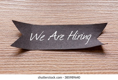 We Are Hiring words written on Black papper with wooden background