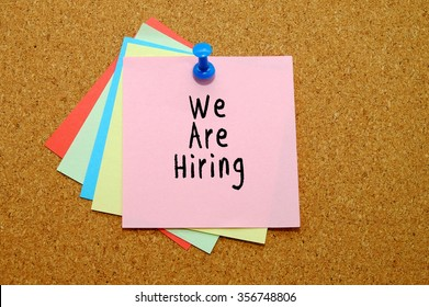 we are hiring written on color sticker notes over cork board background.