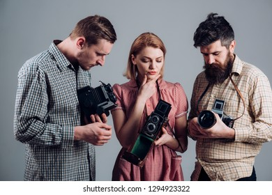 We just click. Group of photographers with retro cameras. Paparazzi or photojournalists with vintage old cameras. Photography studio. Retro style woman and men hold analog photo cameras.
