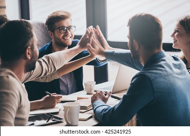 We are leaders on the market! Cheerful young people giving each other high-five with smile while sitting at the office table on business meeting