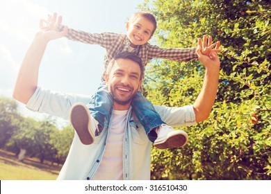 We like spending time together! Low angle view of happy little boy stretching out hands while his father carrying him on shoulders