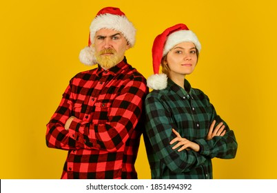 We love christmas. Couple in love enjoy christmas holiday celebration. Family wear santa hats. Entertainment ideas for adults. Santa team. Loving couple yellow background. Christmas magical time.