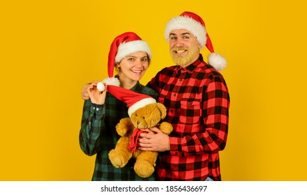 We love christmas. Couple in love with teddy bear soft toy enjoy christmas holiday. Family santa hats. Entertainment ideas for adults. Family holiday. Loving couple yellow background. Christmas time.