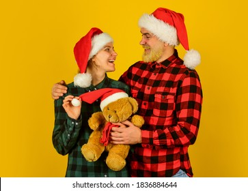We love christmas. Loving couple yellow background. Christmas time. Couple in love with teddy bear soft toy enjoy christmas holiday. Family santa hats. Entertainment ideas for adults. Family holiday.