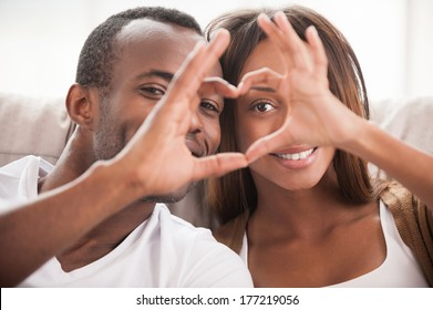 We love each other! Beautiful young African couple sitting close to each other and looking through a heart shape made with their fingers