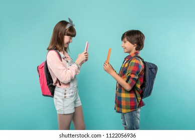 We love gadgets. Inspired charming children standing opposite each other and holding their tablets