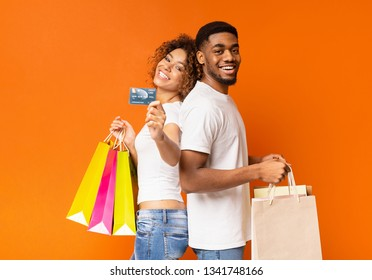 We love our bank! Happy millennial african-american couple with shopping bags and credit card, orange background