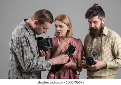 We love photo news. Paparazzi or photojournalists with vintage old cameras. Photography studio. Retro style woman and men hold analog photo cameras. Group of photographers with retro cameras.