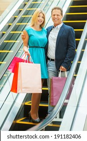 We love shopping together! Full length of cheerful mature couple holding shopping bags and smiling while moving by escalator
