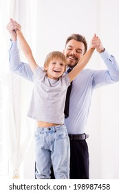 We love spending time together! Happy father in formalwear having fun with his son at home