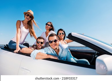 We love spending time together! Group of young happy people enjoying road trip in their white convertible and smiling at camera