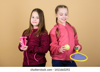 We love sport. Child might excel in completely different sport. Friends ready for training. Ways to help kids find sport they enjoy. Girls cute kids with sport equipment dumbbells and tennis racket.