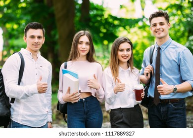 We love studying. Four happy young people showing their thumbs up and smiling while standing close to each other outdoors