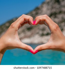 We love the summer - Pink nailed woman hands forming heart shape with mediterranean beach in the background