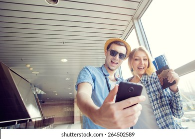 We love traveling! Vacation Selfie. Beautiful young loving couple making selfie by their smart phone while waiting for boarding in the airport.