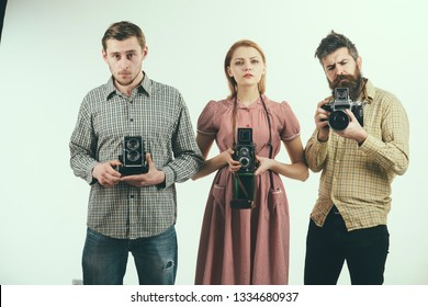 We may snap at any time. Group of photographers with retro cameras. Retro style woman and men hold analog photo cameras. Paparazzi or photojournalists with vintage old cameras. Photography studio.