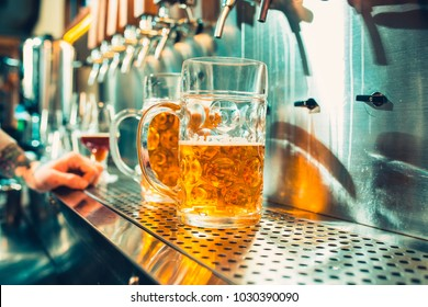 We meet oktoberfest. Hand of bartender pouring a large lager beer in tap. Pouring beer for client. Side view of young bartender pouring beer while standing at the bar counter