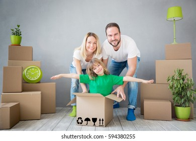 We are moving! Happy family playing into new home. Father, mother and child having fun together. Moving house day and express delivery concept