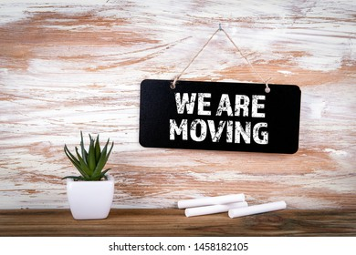 We Are Moving. Small blackboard on the wall with text, positive thinking and looking forward concept