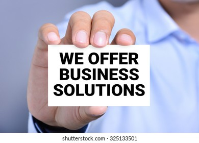 WE OFFER BUSINESS SOLUTIONS message on the card shown by a man