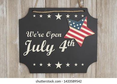 We are open July 4th text Independence Day on a chalkboard with patriotic USA red and blue star on weathered wood