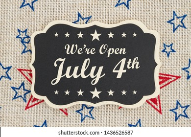 We are open July 4th text for Independence Day on a chalkboard with patriotic USA red and blue stars on burlap