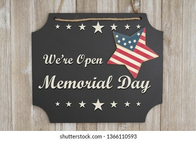 We are open Memorial Day text on a chalkboard with patriotic USA red and blue star on weathered wood
