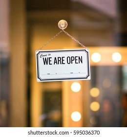 WE ARE OPEN sign board through the glass of store window. Filtered image.