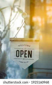We Are Open Sign and chain hangs on a glass storefront or door due to the shop or retail business , Welcome Come On In.