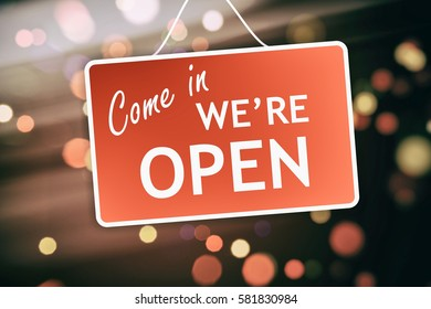 We are open sign hanging on a glass storefront