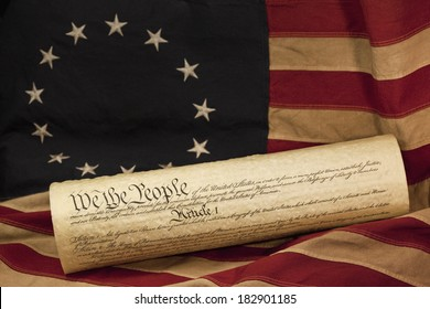 We the People, the opening words of the preamble to the Constitution of the USA, is prominent on the copy of the constitution. The parchment document is lying on an aged colonial era American flag.